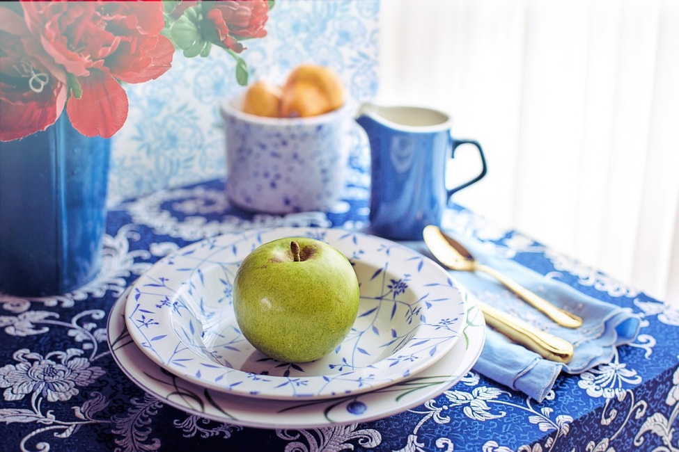 Pretty table setting in blue and white with green apple.